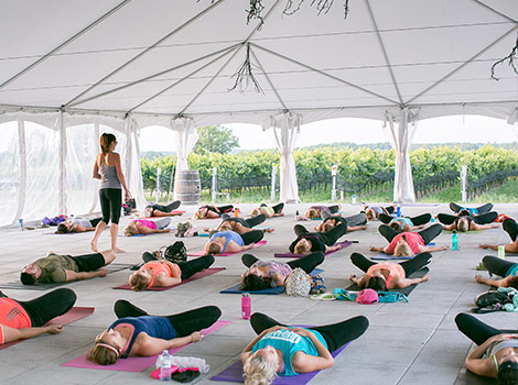Dozens of people doing yoga under a tent in a winery.