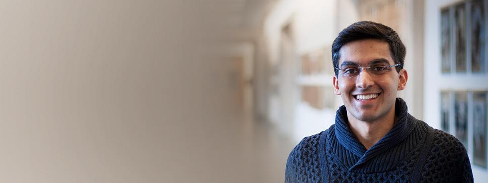 Malik Ladhani, souriant, se tient dans un couloir
