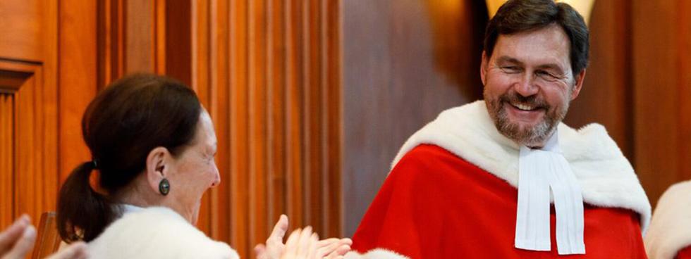 Le juge Richard Wagner, vêtu de sa toge au col d'hermine de la Cour suprême, sourit devant les applaudissements d'une autre juge