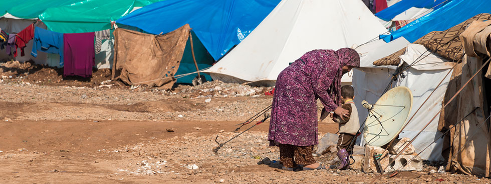A woman and child stand in front of a sea of refugee tents in a desert.
