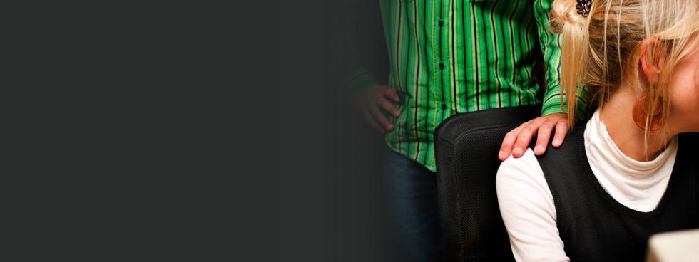 Debout derrière une femme assise, un homme lui pose la main sur l'épaule.
