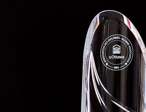 Alumni award trophy in front of a plain backdrop