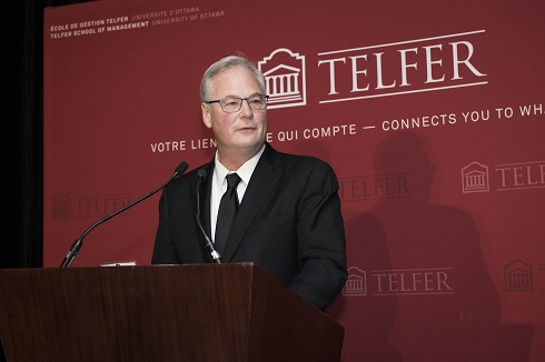 Dr. Jack Kitts speaks at a microphone against the backdrop of a Telfer banner..