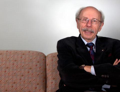 Assis sur un sofa, les bras croisés, le Dr Antoine Hakim arbore un sourire.
