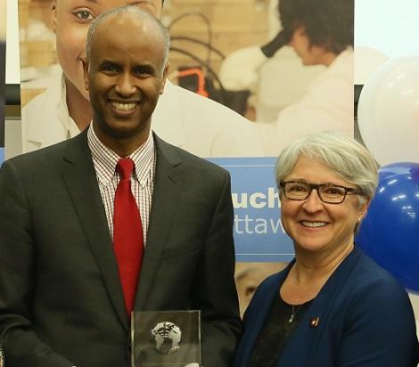 Debout devant une affiche et quelques ballons, Ahmed Hussen et Édith Dumont tiennent un trophée en souriant.