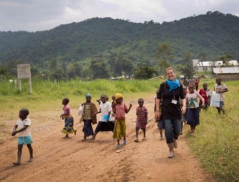 Un groupe d'enfants enjoués marchant sur un terrain de terre avec la souriante Murielle Pallares.