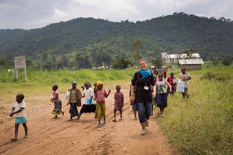 A group of smiling children walking on a dirt road with smiling Murielle Pallares.