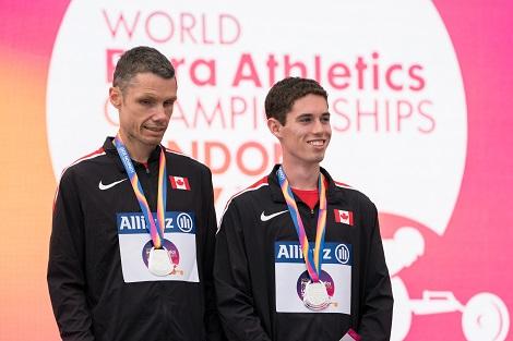 Jason Dunkerley et Jérémie Venne portant des médailles autour de leur cou et placés devant une affiche des Championnats du monde de para-athlétisme