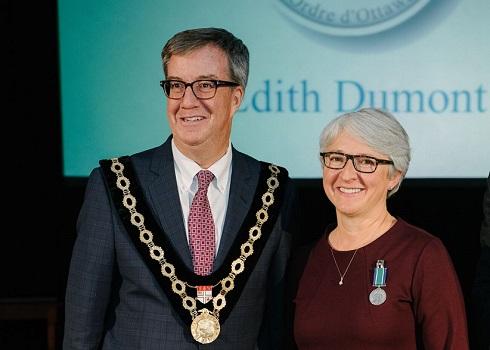 Jim Watson, paré de sa chaîne officielle, se tient à coté d'Édith Dumont, qui porte une médaille épinglée sur son chemisier.