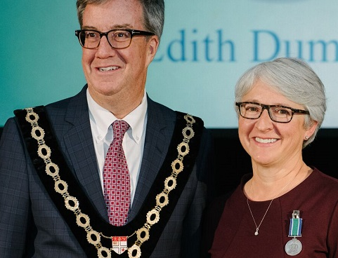Jim Watson, wearing his chain of office, stands beside Édith Dumont, who has an award pinned to her clothing.