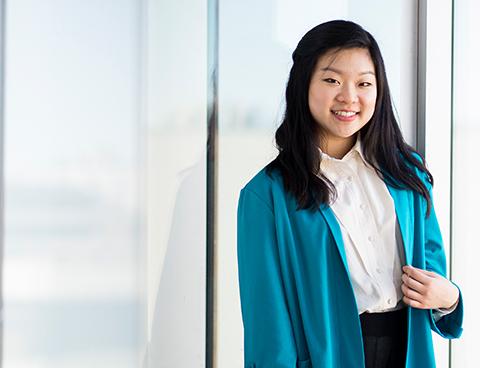 Esther Kim sourit, debout devant une fenêtre.