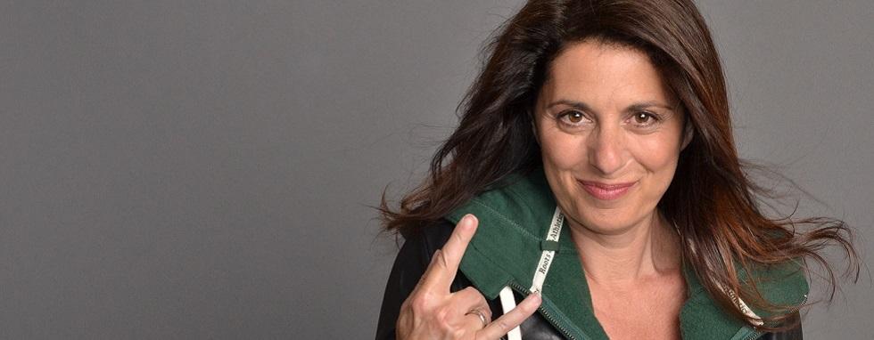 Erica Ehm, tout sourire, faisant le signe emblématique du rock'n'roll avec sa main droite.