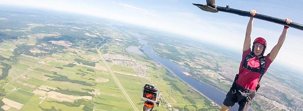 Marc Bjerring est suspendu dans les airs par le patin d'un hélicoptère au-dessus d'un champ et d'une rivière.