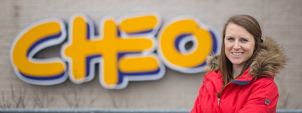 A woman in a winter coat stands outside the Children's Hospital of Eastern Ontario, with the CHEO logo appearing beside her. She is smiling and has her arms crossed.