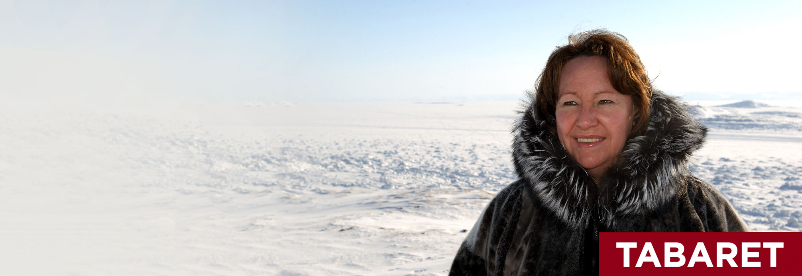 Sheila Watt-Cloutier wearing a fur-lined parka stands smiling in a snow-covered Arctic landscape