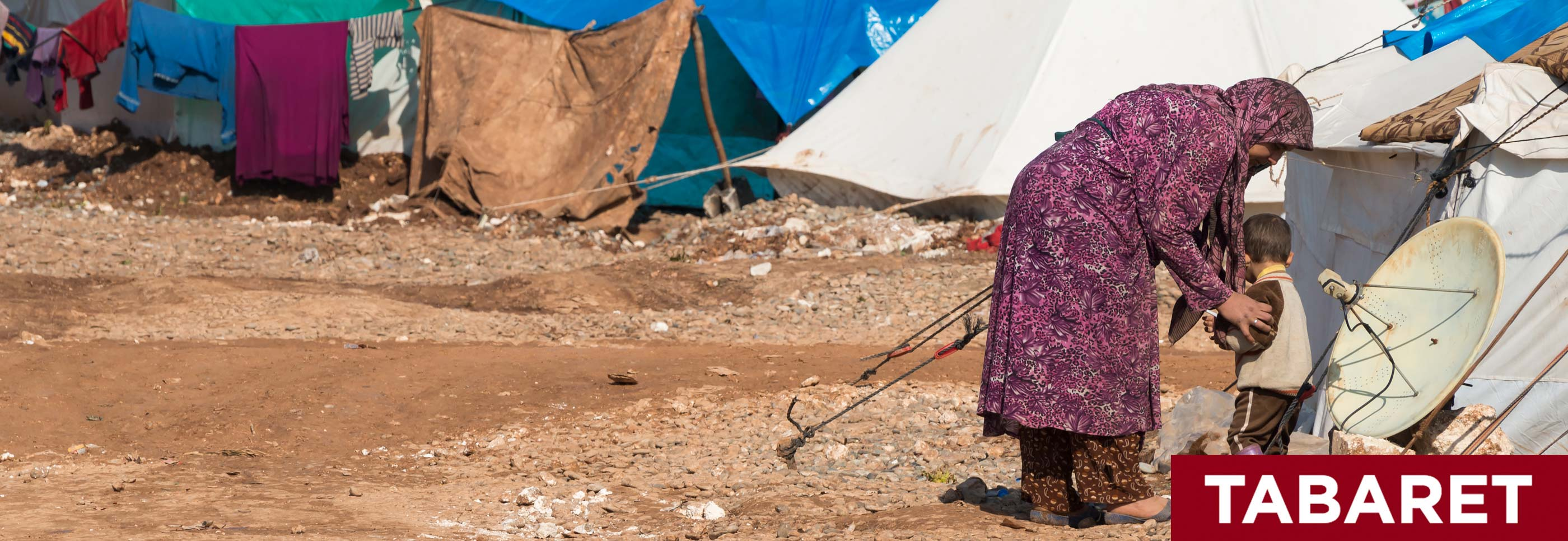 A woman and child stand in front of a sea of refugee tents in a desert