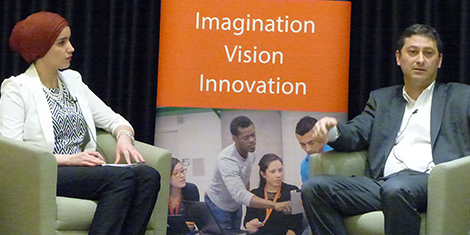 "Marwan Forzley seated on stage beside a uOttawa promotional poster that shows students collaborating on a project beneath the words ""Imagination, Vision, Innovation."""