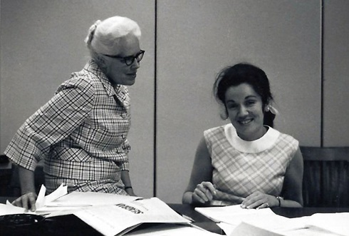 Florence Bird and Monique Bégin side-by-side at a desk covered with papers.