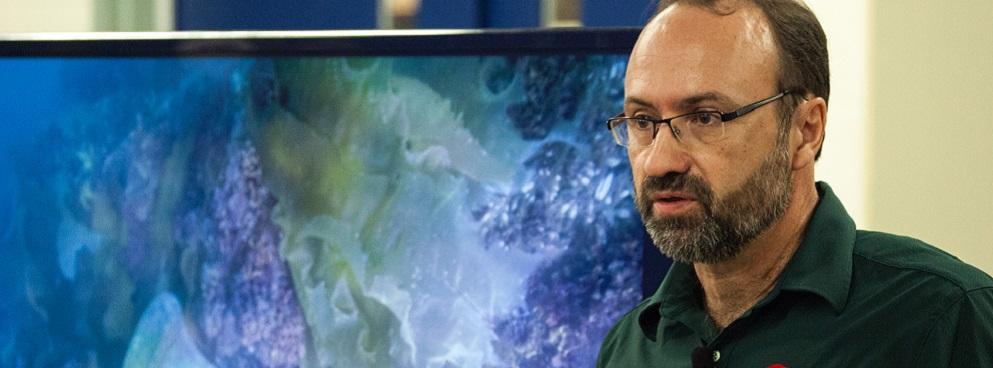 Marc-André Bernier debout devant une image de la cloche du navire NSM Erebus durant une conférence de presse.