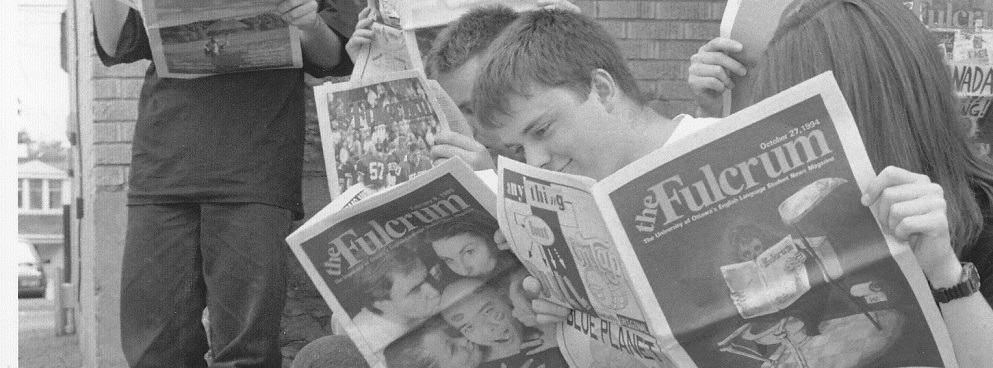 Black and white photo of students reading The Fulcrum in the mid-1980s.