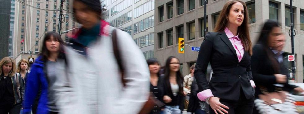 Sarah Saska au coin d'une rue où passent des gens affairés.