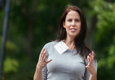 Sarah Saska arborant une étiquette à son nom, les mains tendues en pleine conversation.