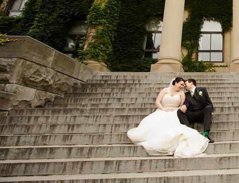 Un couple de jeunes mariés assis sur les marches du pavillon Tabaret se regardent dans les yeux.
