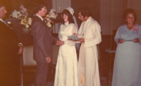 A man and a woman, in wedding clothes, gaze at each other. A priest stands beside them, and two other wedding guests are in the frame.