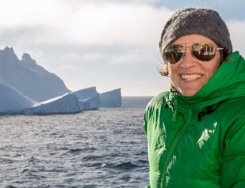 A woman in cold weather gear and sunglasses, against the backdrop of choppy water and a large iceberg.