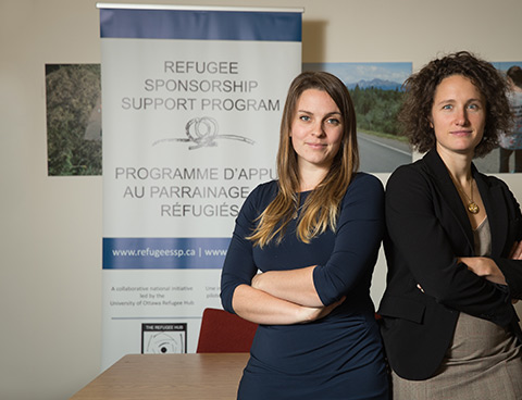 Emily Bates and Katie Black stand next to a sign with the words Refugee Sponsorship Support Program on it.