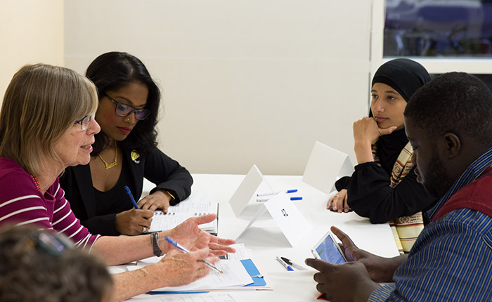 A group of four people, including law students Mayoori Malankov and Assma Basalamah, sit around a table taking notes.