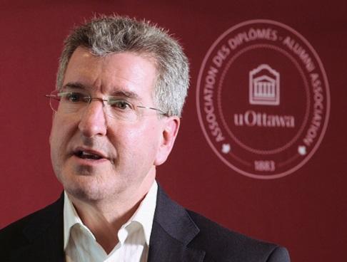 Donald Beauchamp devant la bannière de l'Association des diplômés de l'Université d'Ottawa.