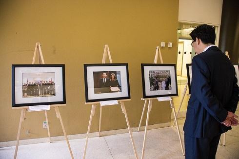 Un homme regarde une rangée de photographies sur des chevalets.