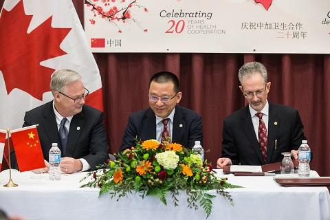Jack Kitts et Weiping Li signent un protocole d'entente, avec Jacques Bradwejn (à droite). Les drapeaux du Canada et de la Chine figurent à l'arrière-plan.