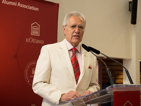 Alex Trebek at the podium on a small stage inside the reception hall for lectures.