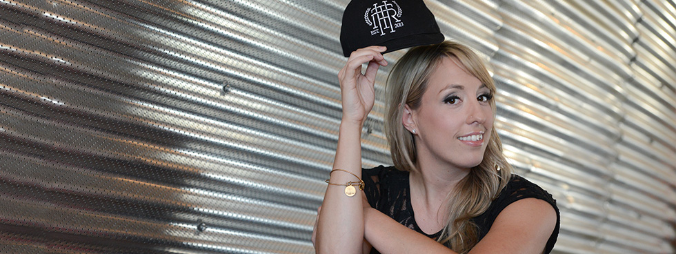 Danika Gagnon assise sur une chaise, souriant et tenant une casquette au-dessus de sa tête.