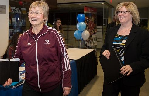 Sue Hylland et Carla Qualtrough passent devant une table d'inscription en souriant et en portant des cahiers de notes. Des ballons à l'arrière-plan créent une atmosphère de fête.