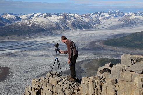 Luke Copland est debout sur une falaise surplombant un glacier au Yukon.
