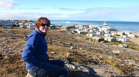 Jackie Dawson, avec les maisons de Pond Inlet en arrière plan.