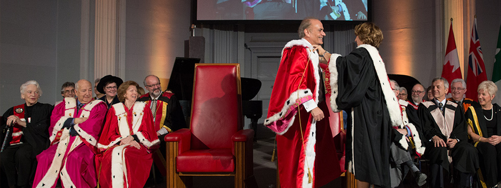 Mona Nemer adjusts Calin Rovinescu's ceremonial robe as they stand on a stage with a video screen in the background and other members of the senate and board of governors seated.