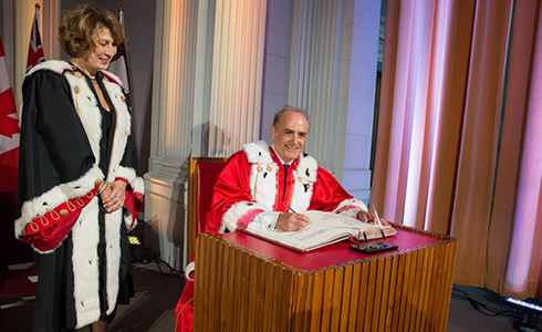 Calin Rovinescu seated in ceremonial robes signs a book as Mona Nemer, also in ceremonial robes, stands next to him.