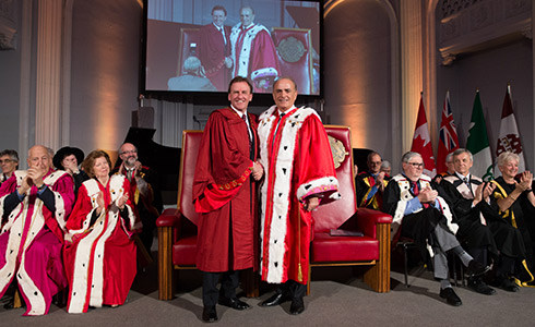 University of Ottawa President Allan Rock shakes hands with Chancellor Calin Rovinescu surrounded by others seated in ceremonial robes on a stage.