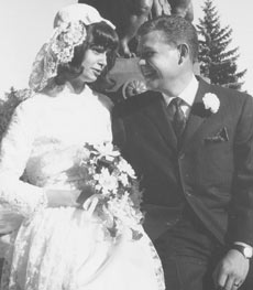 A woman and a man in wedding clothes smile at each other.