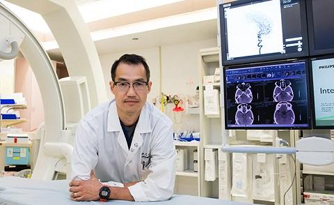 Le Dr Cheemun Lun se penche au-desses d'une table de radiologie avec des scans de cerveau en arrière-plan.