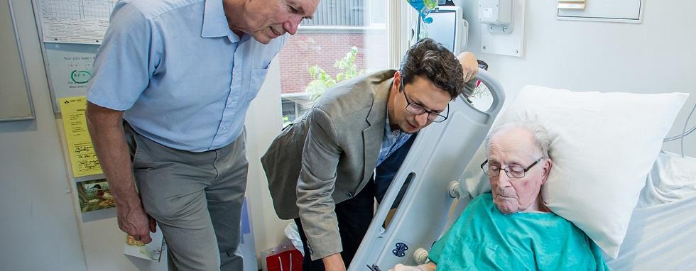 Dr Dale Corbett et Dr Dar Dowlatshahi au chevet d'un patient qui consulte une tablette.