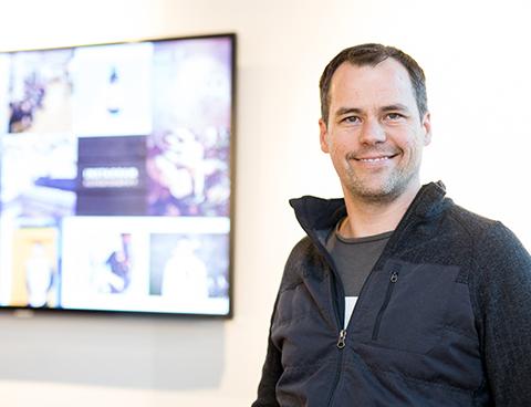 Jean-Michel Lemieux, souriant, se tient devant un mur où est installé un écran vidéo montrant des images et des statistiques brouillées.