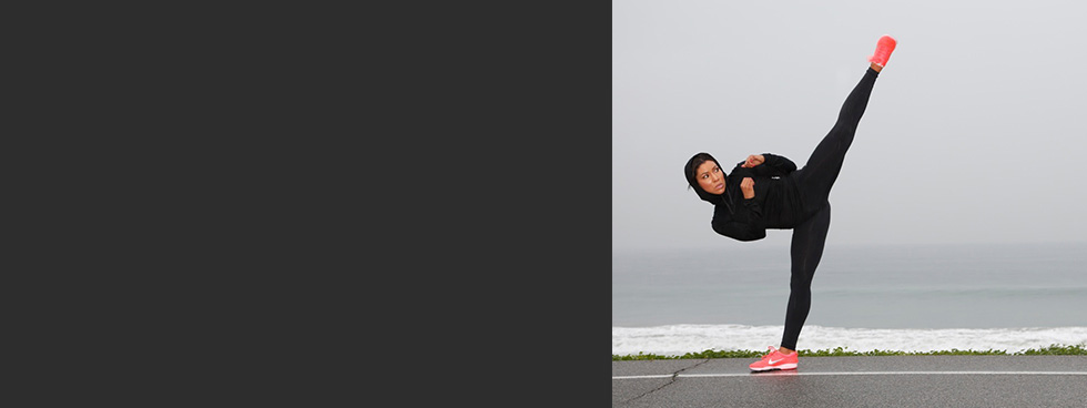 Jeanette Jenkins doing a side kick with the ocean in the background.