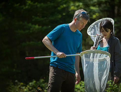 Jeremy Kerr and Rosana Soares, both holding nets, look into one of the nets.