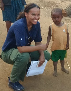 A woman holding a notebook crouches to shake the hand of a young boy.