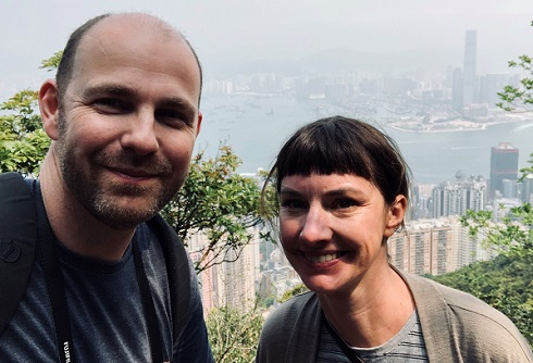 Keri Ryan and Ben Collinge stand together at the top of a hill, with high-rise buildings and Hong Kong's Victoria Harbour in the distance below.